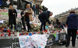 Des volontaires entretiennent les hommages place de la République le 30 novembre 2015 en mémoire des victimes des attentats du 13 novembre. La veille, des heurts ont éclaté entre forces de l'ordre et manifestants.