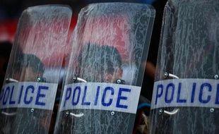 Des policiers égyptiens derrière leur bouclier de protection le 6 décembre 2014 au stade du Caire