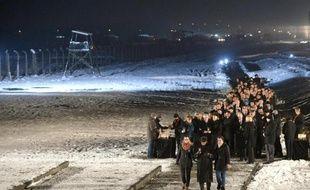 Le président polonais Bronislaw Komorowski (c) et des invités allument des bougies en mémoire des victimes du camp nazi d'Auschwitz, le 27 janvier 2015 à Oswiecim, en Pologne